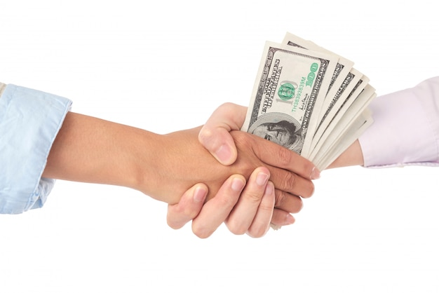 Closeup of handshake with dollar bills in the middle Free Photo