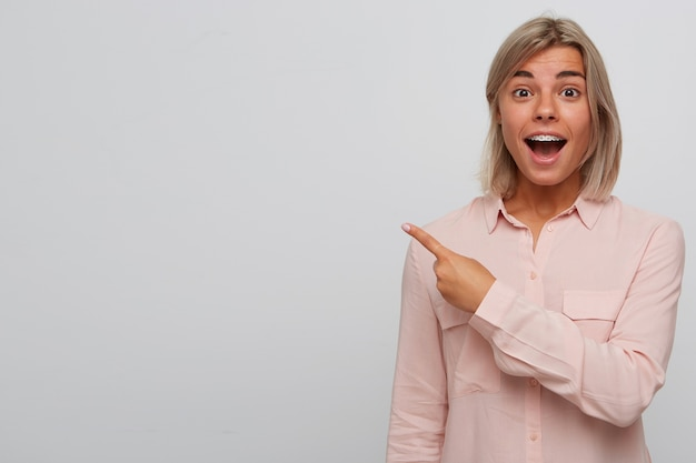 Closeup of happy amazed blonde young woman with braces on teeth and opened mouth wears pink shirt looks surprised and points to the side with finger isolated over white wall Free Photo