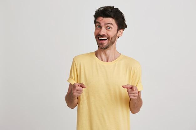 Il primo piano del giovane barbuto attraente felice indossa sorridere giallo della maglietta e indica alla macchina fotografica con entrambe le mani isolate su bianco Foto Gratuite