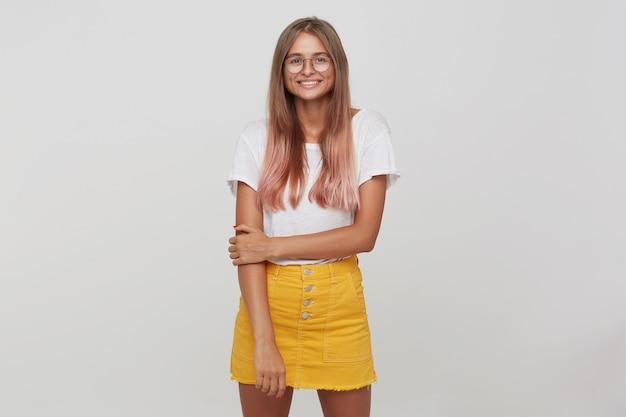 Primo piano di felice bella giovane studentessa con capelli rosa pastello tinti lunghi indossa maglietta, gonna gialla e occhiali in piedi, sembra allegro e posa isolato sopra il muro bianco Foto Gratuite