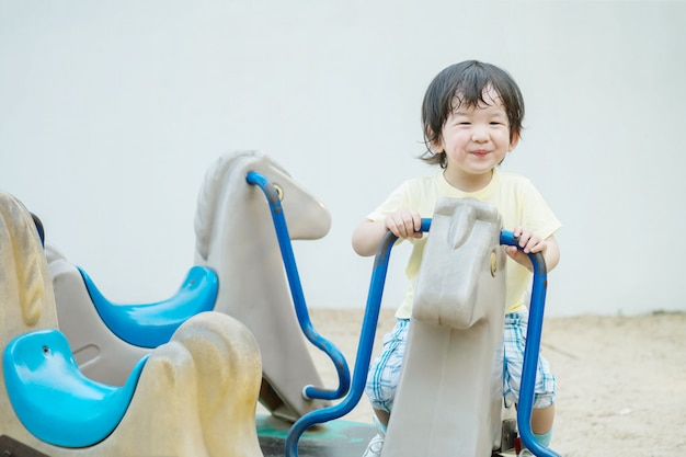 Closeup happy kid with smile face play carousel toy in the playground Premium Photo
