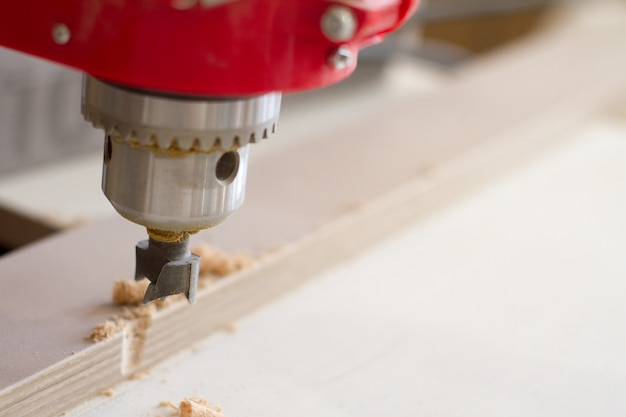 Closeup of the head of the drilling machine with nozzle in the furniture workshop Premium Photo