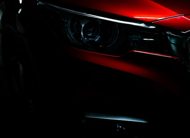 Closeup headlight of shiny red luxury suv compact car Premium Photo