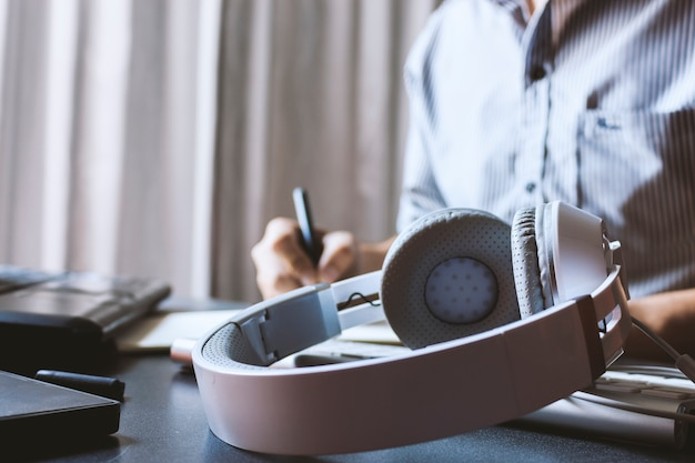 Closeup headphones and businessman  working on laptop in office Premium Photo