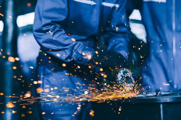 Closeup heavy steel worker using electric wheel grinding disc cuting metal plate in workplace Premium Photo