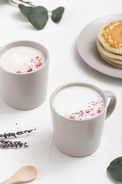 Primo piano alto angolo di ripresa di una tazza di caffè e alcune decorazioni sul tavolo bianco Foto Gratuite