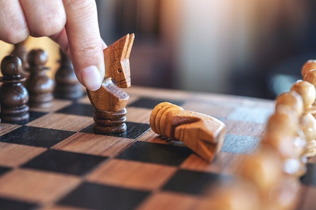 Closeup image of a hand holding and moving a horse to win another horse in wooden chessboard game Premium Photo