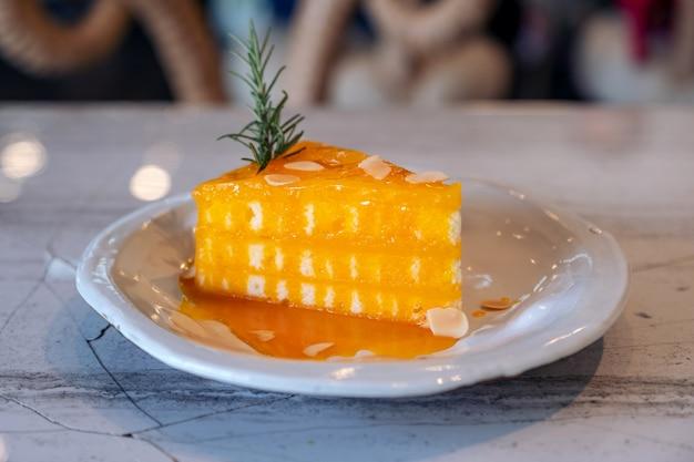 Крупным планом изображение кусок апельсинового торта на керамической тарелке Premium Фотографии