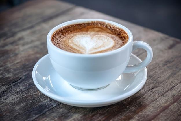 Крупным планом изображение белых чашек горячего кофе на старинный деревянный стол в кафе Premium Фотографии
