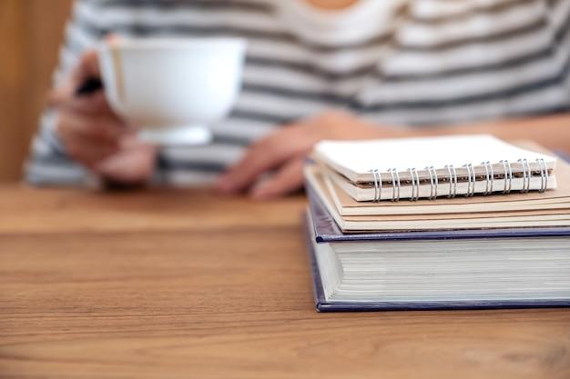 木製のテーブルの上の本やノートとコーヒーを飲む女性のクローズアップ画像 Premium写真