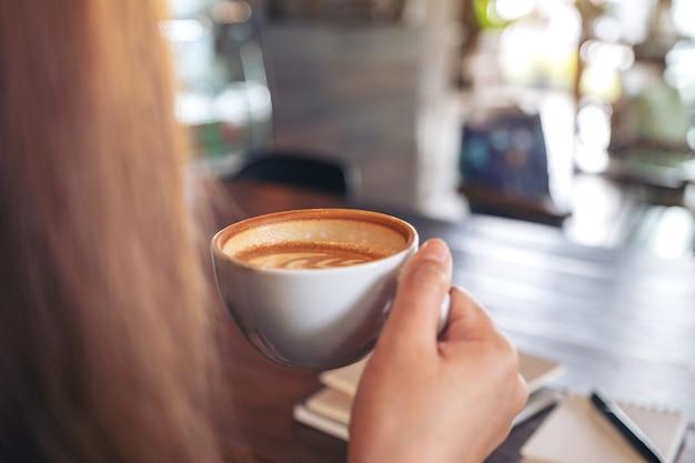 ホットコーヒーを保持し、飲む女性のクローズアップ画像 Premium写真