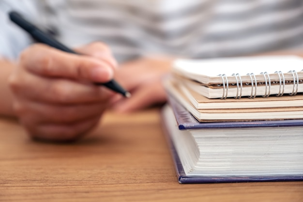 ノートや木製のテーブルの本に書くためにペンを持っている女性の手のクローズアップ画像 Premium写真