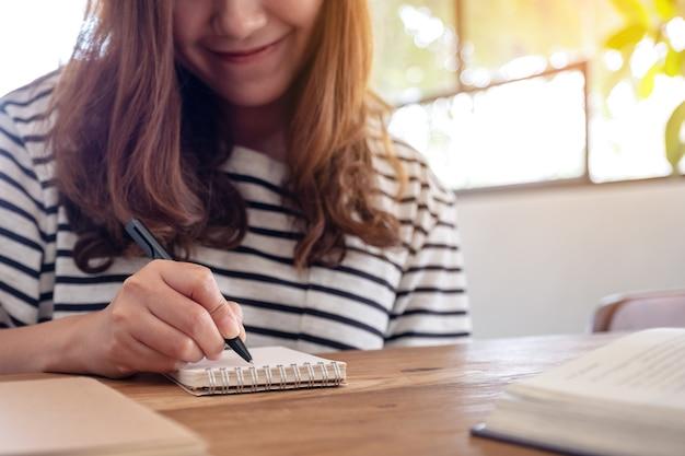 学習しながら空白のノートブックと木製のテーブルの本に書いている女性のクローズアップ画像 Premium写真