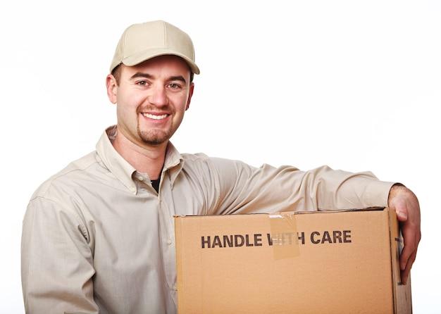 Крупным планом изображение улыбающегося молодого кавказского доставщика с посылкой Premium Фотографии