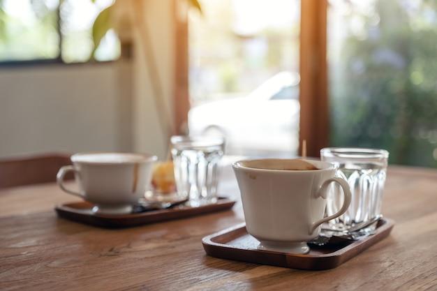 ホットコーヒーの白いマグカップとカフェの木製テーブルの上の水のグラスのクローズアップ画像 Premium写真