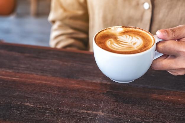 Крупным планом изображение женских рук, держащих чашку горячего кофе на деревянном столе в кафе Premium Фотографии