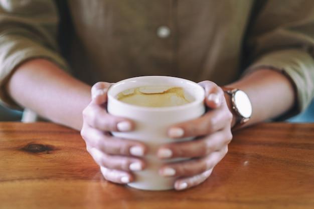 Крупным планом изображение женских рук, держащих чашку горячего кофе на деревянном столе Premium Фотографии