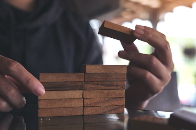 Closeup image of people playing and building wooden puzzle game Premium Photo