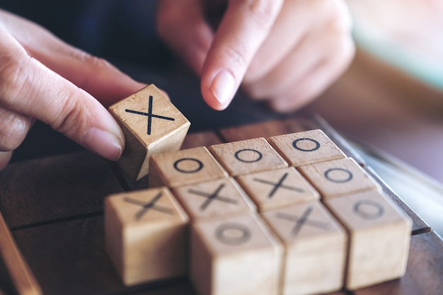 Closeup image of people playing wooden tic tac toe game or ox game Premium Photo
