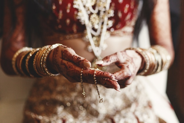 Closeup of indian bride's hands covered with mehndi and holding Free Photo