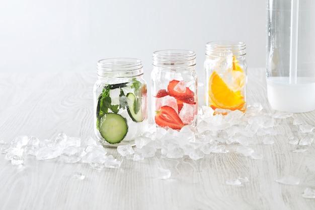 얼음과 다양한 충전재 오렌지, 딸기, 오이, 민트가있는 근접 촬영 항아리는 탄산수로 신선한 수제 레모네이드를 만들기 위해 준비되었습니다. 무료 사진
