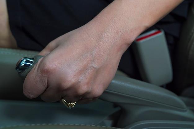 Closeup of lady's hand pulls car hand brake Free Photo