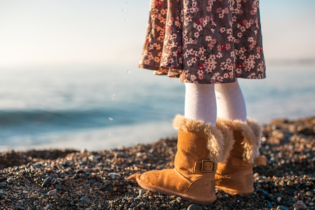Closeup of legs little girl in cozy fur boots background the sea Premium Photo