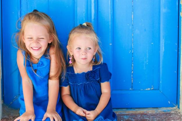 Closeup of little adorable girls sitting near old blue door in greek village, emporio, santorini Premium Photo
