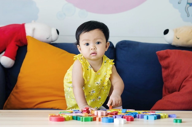 Closeup little girl play wooden jigsaw puzzle toy on sofa in the living room background Premium Photo