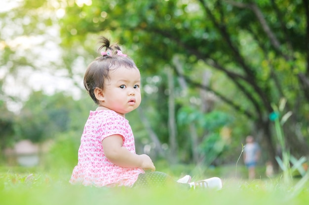 Closeup little girl sit on grass floor in the park with sun light background in cute motion Premium Photo