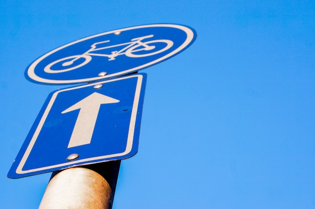 Closeup and look up view traffic signs of bicycle lane and navigation arrow on clear blue sky background. Premium Photo