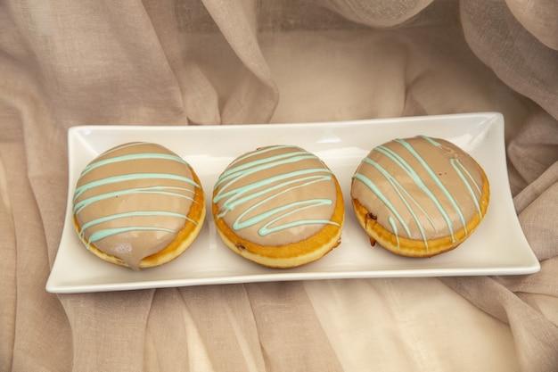 Primo piano di amaretti con topping al caramello su un piatto sotto le luci Foto Gratuite