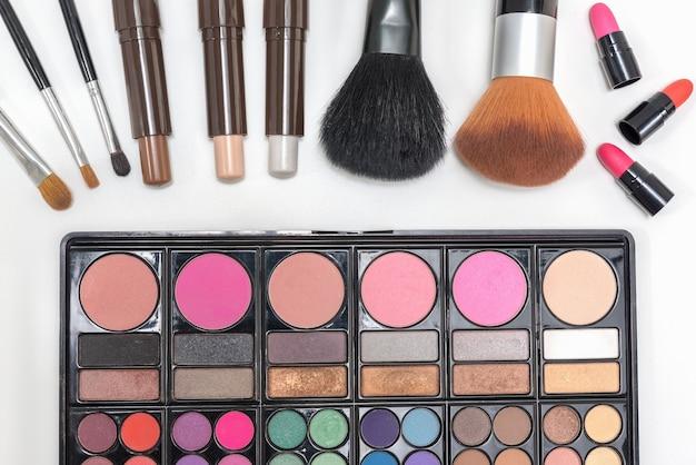 Closeup makeup cosmetics palette lipstick and brushes Free Photo