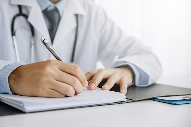 Closeup of male doctor's hands taking notes or fills in the client's medical card or prescribes medication. Premium Photo