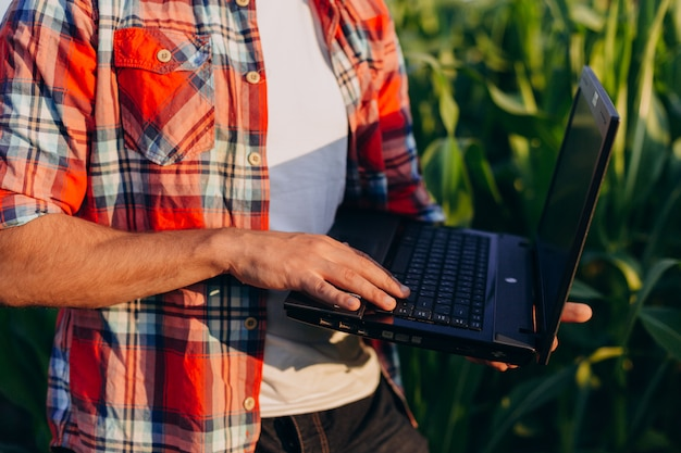 Closeup male hand on the laptop. farmer standing in a field holding open notebook. Premium Photo