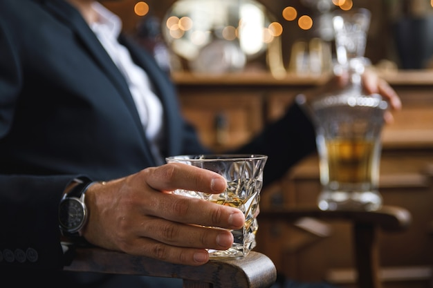 Closeup of male hand with a glass of expensive whiskey Premium Photo