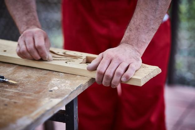Closeup of male hands carpenter using sandpaper to sand wooden detail. Premium Photo