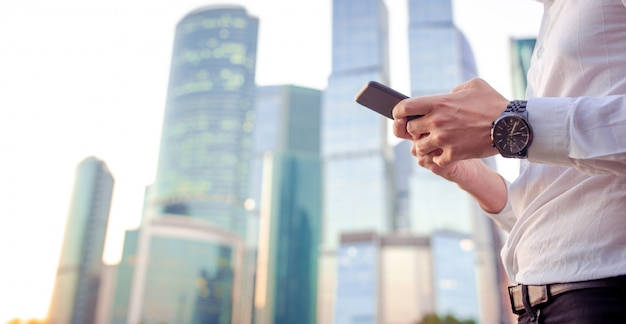 Closeup of male hands is holding cellphone outdoors on the street. man using mobile smartphone. Premium Photo