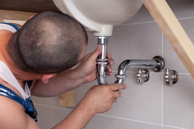 Closeup male plumber in blue denim uniform fixing sink in bathroom with tile wall