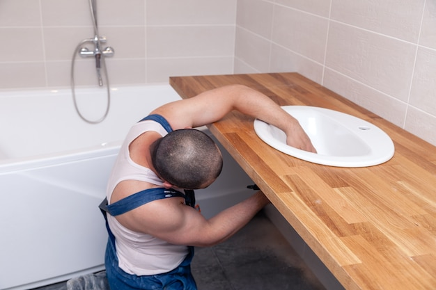 Closeup male plumber worker in blue denim uniform, overalls, fixing sink in bathroom with tile wall. professional plumbing repair service, installation water pipes, man mounted sewer drain Premium Photo