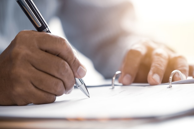 Closeup male senior hand writing sign contract document concept Premium Photo