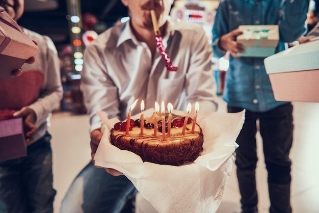 Closeup of man holding birthday cake with candles Premium Photo