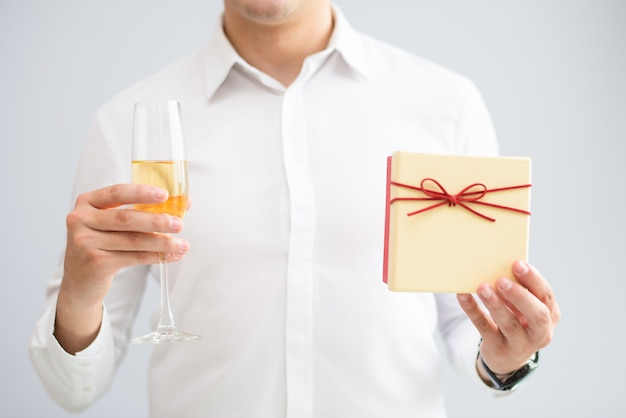 Closeup of man holding glass with champagne and gift box Free Photo