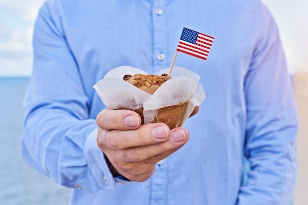 クローズアップ男はアメリカのアメリカの国旗とカップケーキを保持します Premium写真