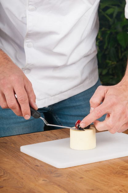 Closeup of man putting berries on peace of ice-cream at table Free Photo