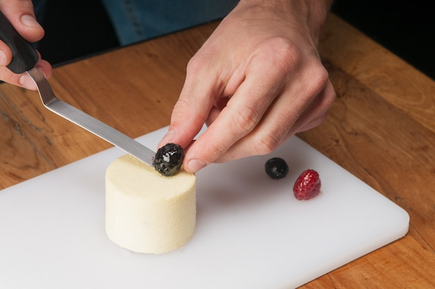 Closeup of man putting berry on peace of ice-cream at table Free Photo