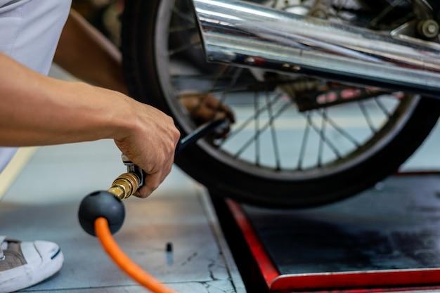 Closeup man's hand checking tires air with a pressure gauge in auto repair service Premium Photo