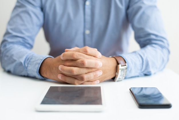 Closeup of man sitting at desk with tablet and smartphone Free Photo