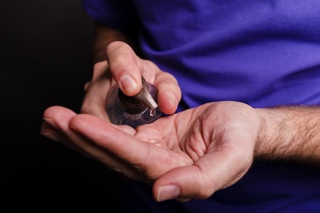 Primo piano di un uomo che utilizza un disinfettante per le mani sul nero Foto Gratuite