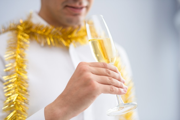 Closeup of man wearing tinsel and drinking champagne Free Photo
